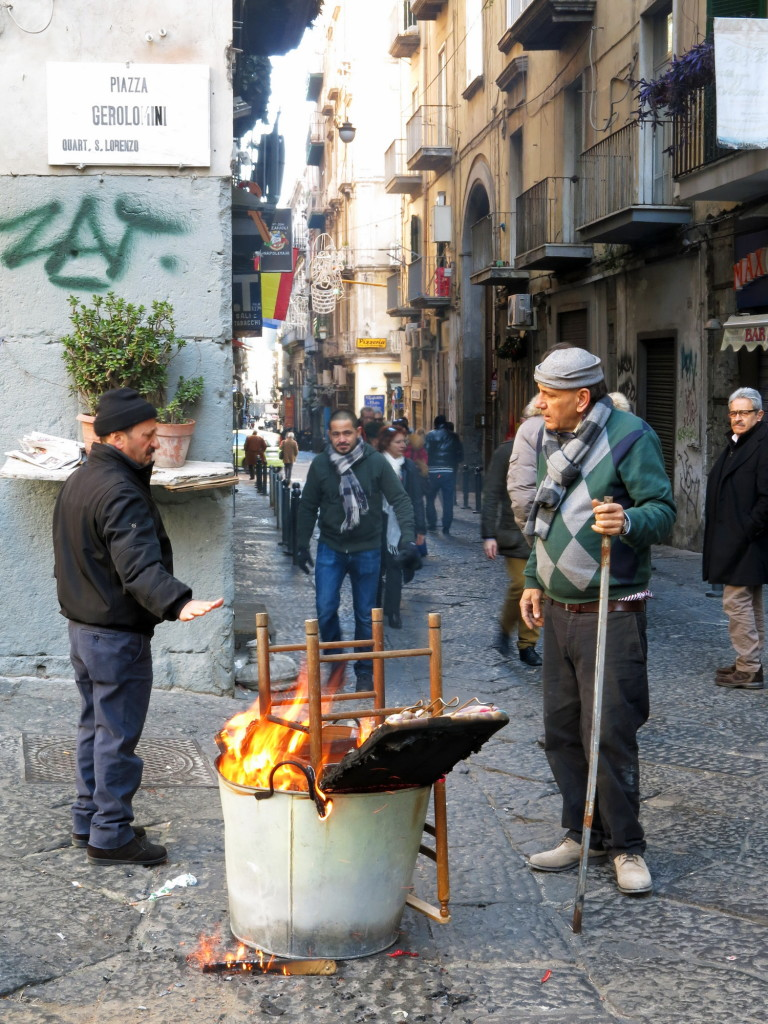 A small trash fire in front of a cathedral in the historic quarter on Via dei Tribunali, one of the most popular streets for tourists to visit in Naples.