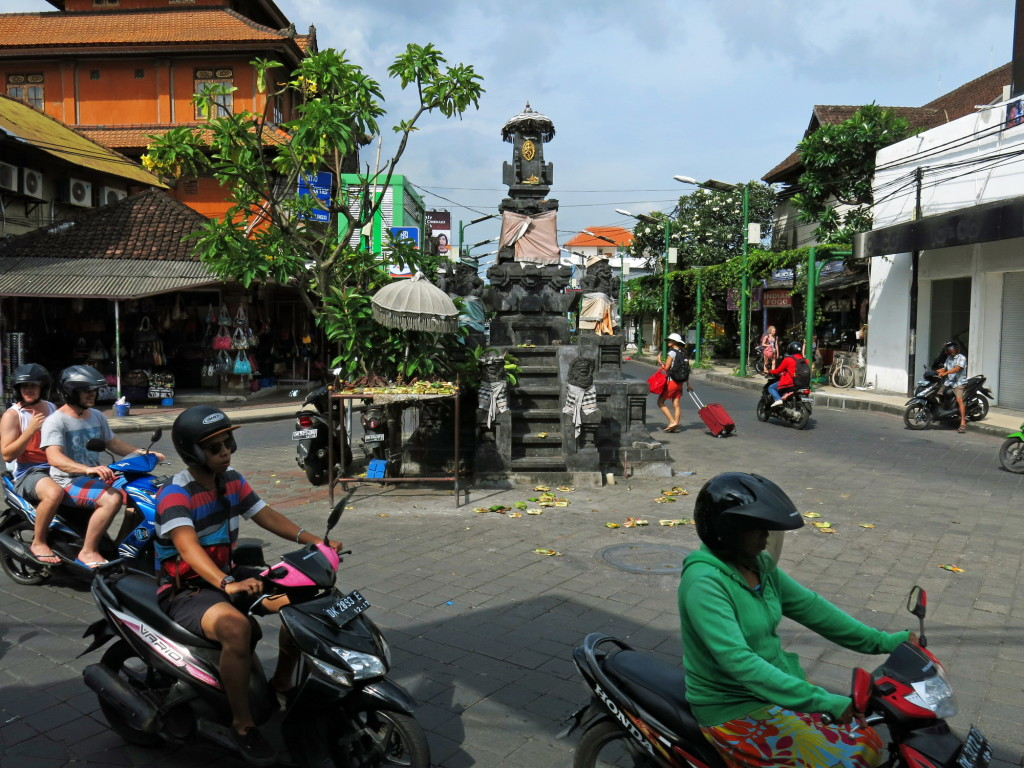 A shrine in the center of this traffic circle in Kuta receives dozens of offerings each day. Many are placed on the street and others on the table.