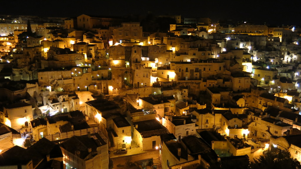 The sassi lit up at night.