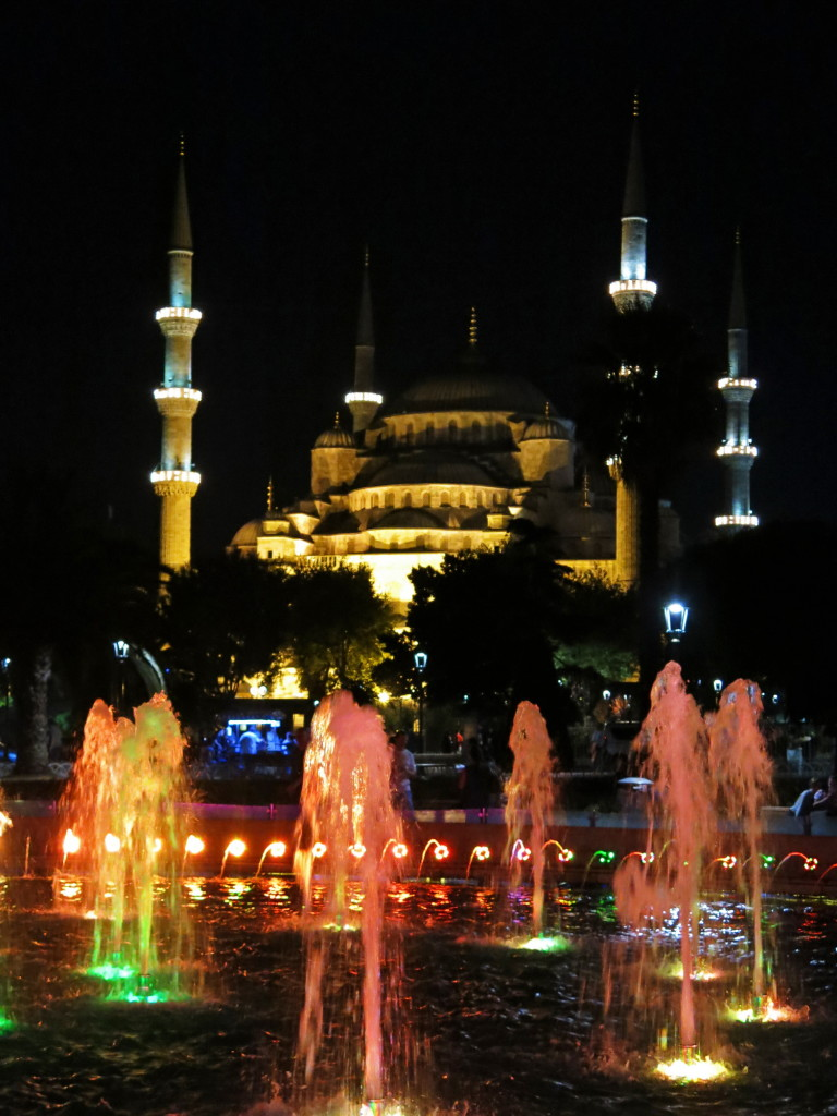Blue Mosque at night with colorful fountain.