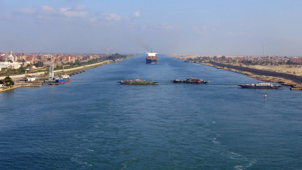 Ferries race across the Suez Canal between the never-ending train of cargo ships.